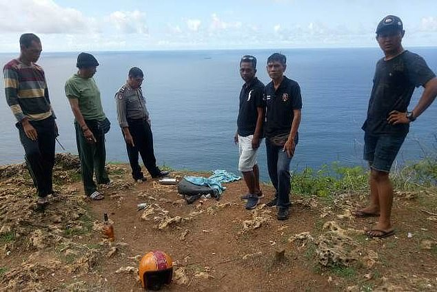 Local officials stand at the site where Mr Roth's belongings were discovered close to the cliff edge on Monday morning
