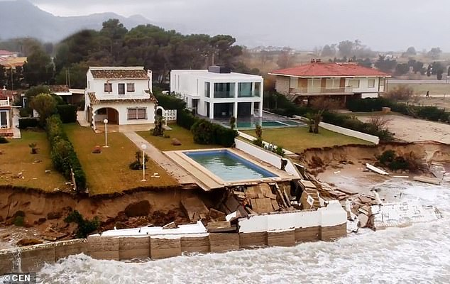 A swimming pool was left hanging precariously over the ocean on Spain's Costa Blanca after the land underneath was washed away by the storm