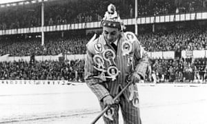 A punter with a bobble hat and a number of rosettes at a snowy White Hart Lane in 1963.