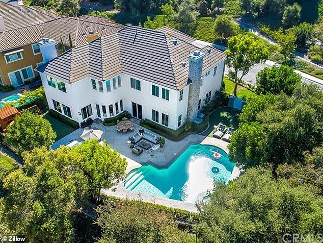 Ready to take a dip! The Bravo-lebrity'slush backyard boasts a swimming pool, spa area, and patio with a BBQ and a grassy lawn