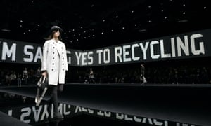 Model walks Tod's catwalk with a background that reads: 'I'm saying yes to recycling'.