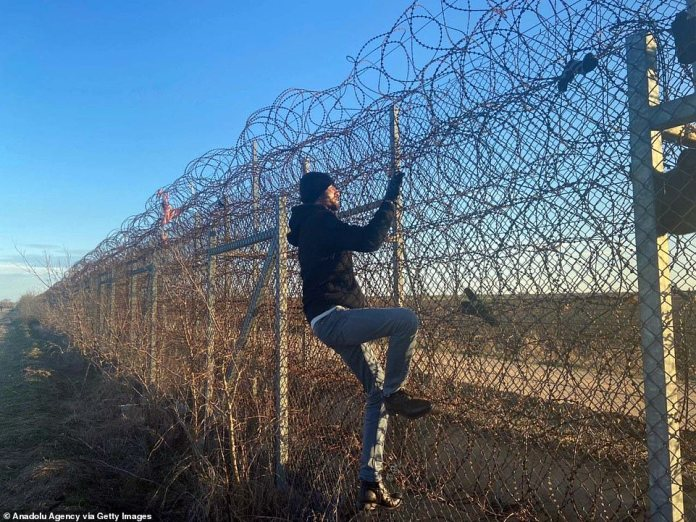 A migrant climbs barbed-wire on Turkey's border with Greece in Edirne, Turkey on February 28. Desperate scenes unfolded on Friday at a border crossing near the Turkish city of Edirne after Turkish police and border guards were ordered to stand aside and allow hundreds of people through