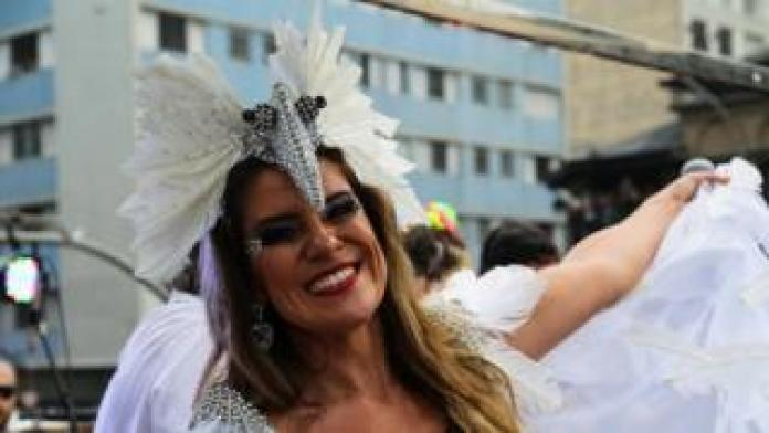 A festival-goer dances in a carnival outfit