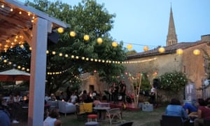 Garden with fairy lights, stage and people drinking