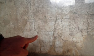 An archaeologist points to engravings on the wall of the Casa della Nave Europa in Pompeii.