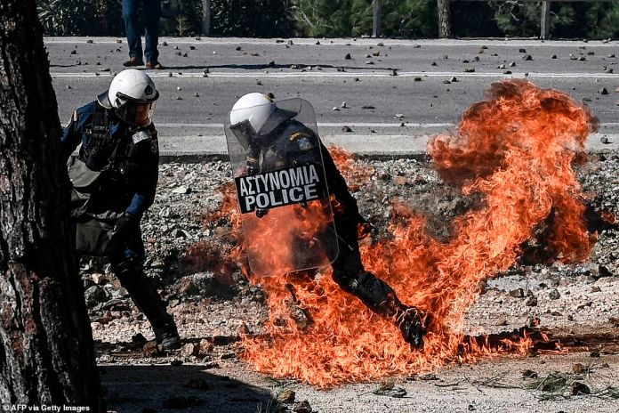Riot police on the Greek island of Lesbos today fired tear gas to disperse hundreds of protesters against the creation of a new detention centre for migrants. A police officer is pictured running away from flames from a petrol bomb