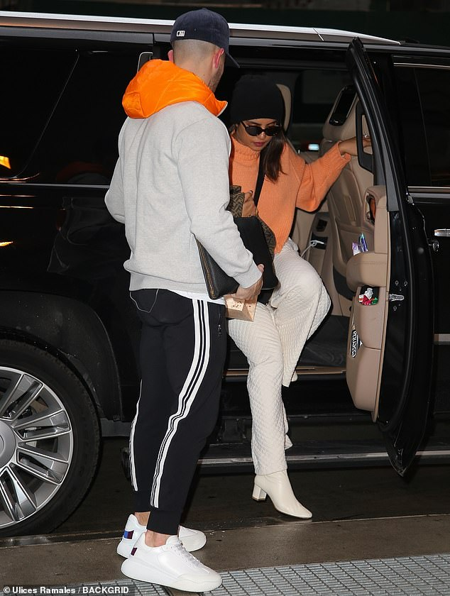 Traveling in style: Her raven tresses were covered up with a black toque, and she carried her Fendi jacket in one arm