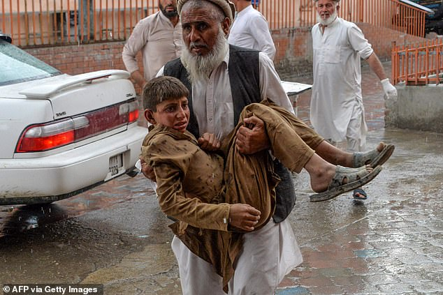 A volunteer carries an injured youth to hospital, following a bomb blast in Haska Mina district of Nangarhar Province in Afghanistan on October 18, 2019