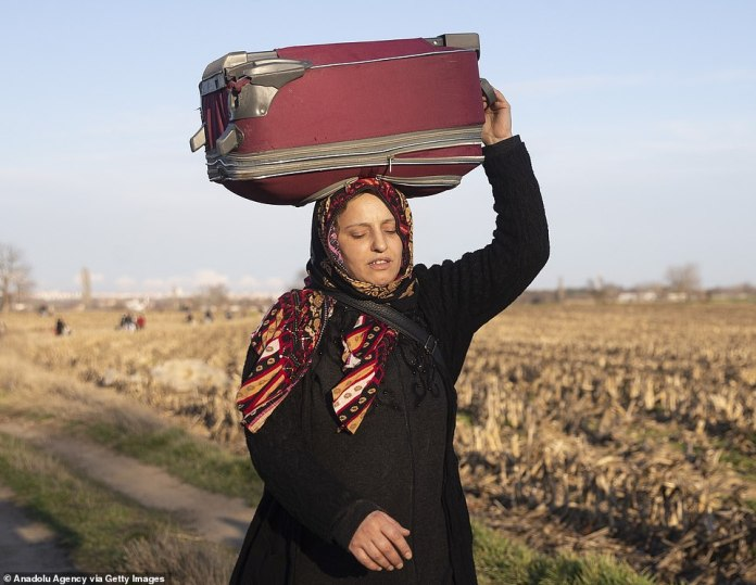 A woman carries a suitcase as she makes her way through the countryside on her way to the Turkish border crossing