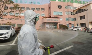 A South Korean health official sprays disinfectant in front of a hospital in Cheongdo county near Daegu.