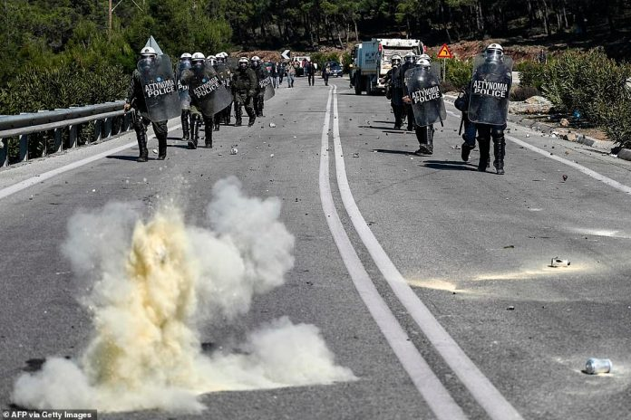 Greek anti-riot police march along a road as they clash with as demonstrators protesting against the construction of a new controversial migrant camp near the town of Mantamados