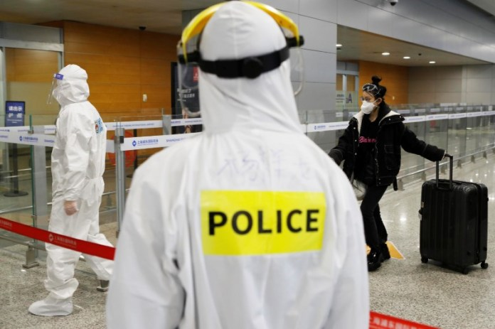 © Reuters. Police officer in a protective suit keeps watch on inbound travellers at Shanghai Pudong International Airport following a global outbreak of coronavirus disease