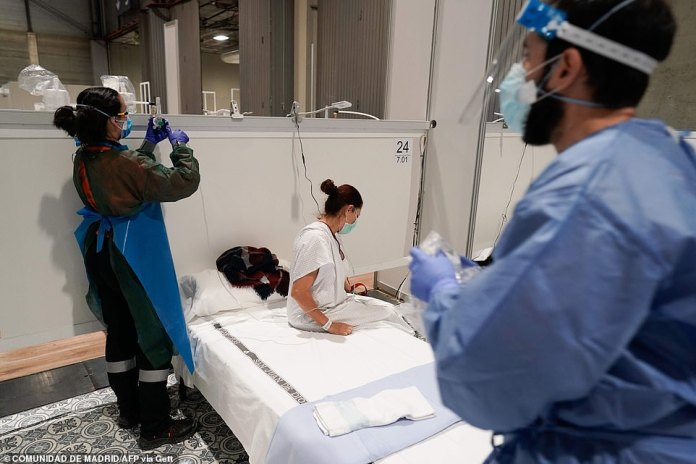 A woman who is sick with coronavirus climbs into bed at a temporary hospital that has been set up in Madrid as the virus grips Spain
