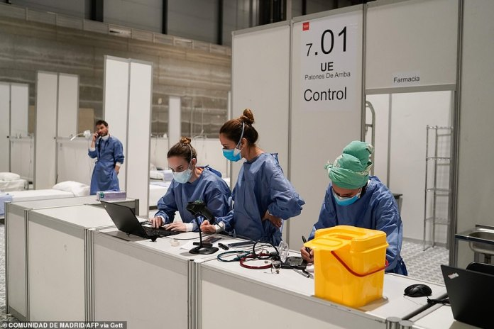 Medics work at the pharmacy of a temporary medical shelter which has been set up for coronavirus patients at a convention centre in Madrid