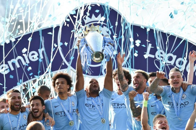TOPSHOT - Manchester City's Belgian defender Vincent Kompany (C) holds up the Premier League trophy after their 4-1 victory in the English Premier League football match between Brighton and Hove Albion and Manchester City at the American Express Community Stadium in Brighton, southern England on May 12, 2019. - Manchester City held off a titanic challenge from Liverpool to become the first side in a decade to retain the Premier League on Sunday by coming from behind to beat Brighton 4-1 on Sunday. (Photo by Glyn KIRK / AFP) / RESTRICTED TO EDITORIAL USE. No use with unauthorized audio, video, data, fixture lists, club/league logos or 'live' services. Online in-match use limited to 120 images. An additional 40 images may be used in extra time. No video emulation. Social media in-match use limited to 120 images. An additional 40 images may be used in extra time. No use in betting publications, games or single club/league/player publications. /         (Photo credit should read GLYN KIRK/AFP via Getty Images)