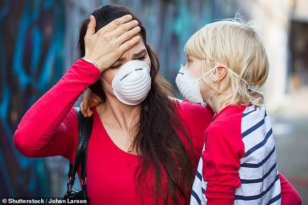 A women endures a migraine while wearing a protective mask and carrying a child wearing a stripey top (stock)