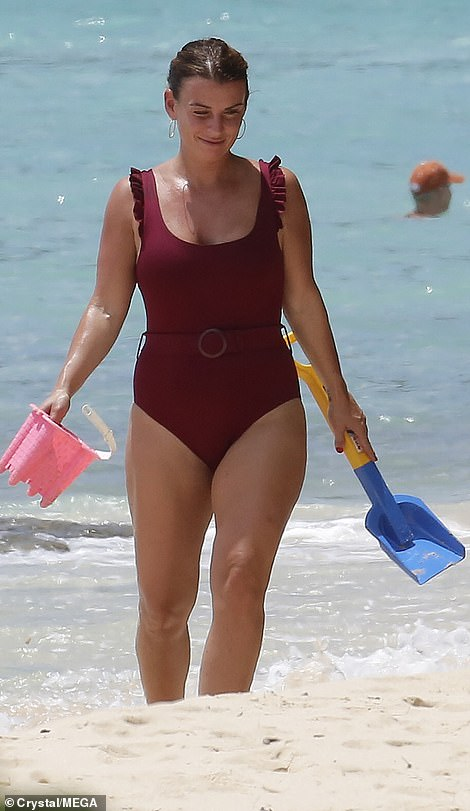 Coleen Rooney catches the eye in a burgundy swimsuit as she hits the beach in Barbados