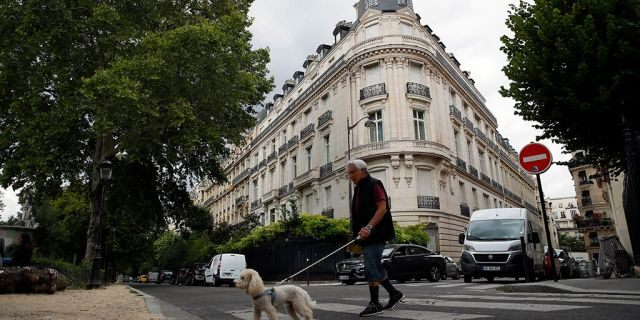A man walks his dog next to an apartment building owned by Jeffrey Epstein in the 16th district in Paris, Tuesday, Aug. 13, 2019. France's government wants prosecutors to open an investigation into Jeffrey Epstein's links to France following his death in a Manhattan jail cell. U.S. authorities say Epstein had a residence in Paris and used a fake Austrian passport to travel to France in the 1980s.