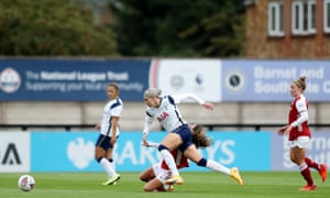 Alanna Kennedy of Tottenham Hotspur shakes off the challenge of Arsenal's Danielle van de Donk and surges forward.