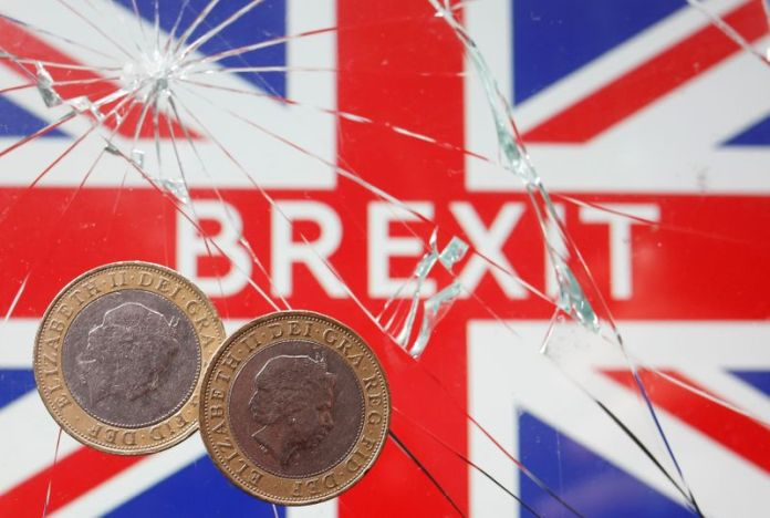 © Reuters. FILE PHOTO: A pound coins are placed on broken glass and British flag in this illustration picture taken