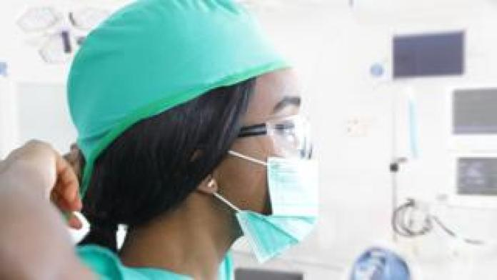 A medical worker puts on a protective mask
