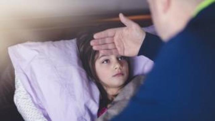father feeling girl's forehead for temperature