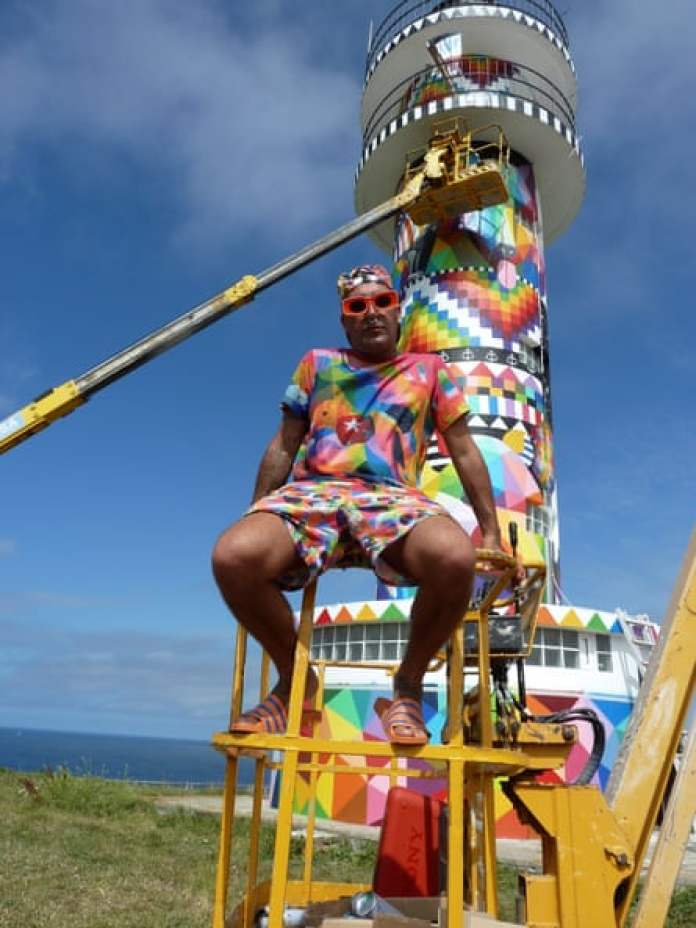 Okuda San Miguel poses next to his mural on the Ajo lighthouse.