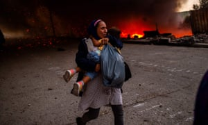 A woman flees with a child as the fire burns in Moria camp on Wednesday.