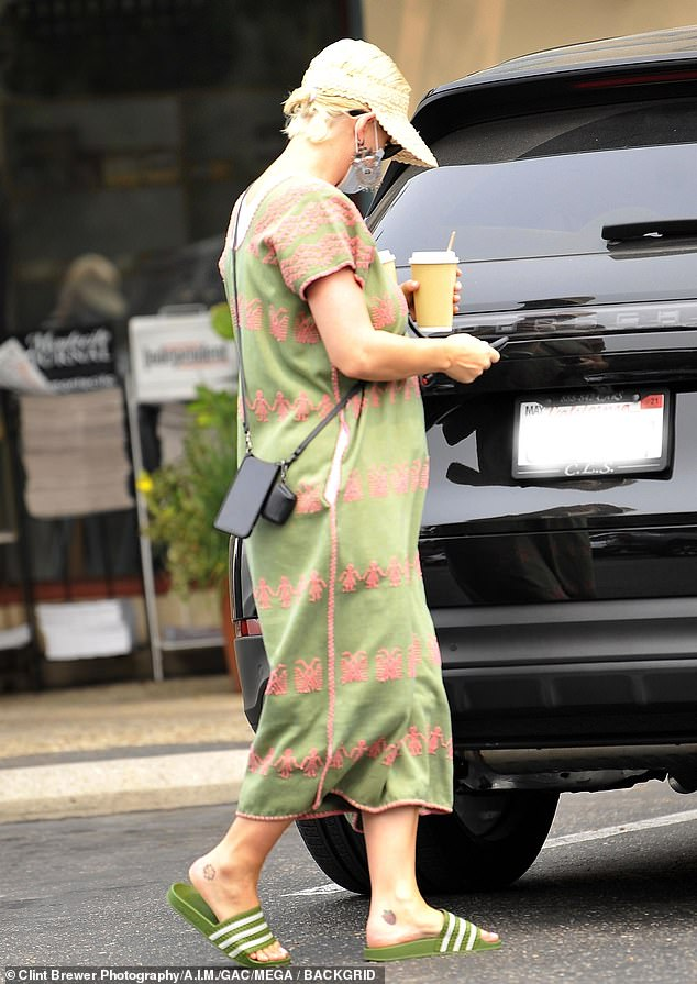 Covered up:The 35-year-old pop star hid her post-baby body beneath a green Bohemian style midi dress that was covered in intricate pink embroidery