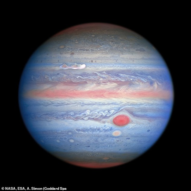 NASA says Hubble's near infrared imaging, combined with ultraviolet views, provides a unique panchromatic look at Jupiter (pictured)  that offers insights into the altitude and distribution of the planet's haze and particles. It also makes the gas giant look like a gobstopper