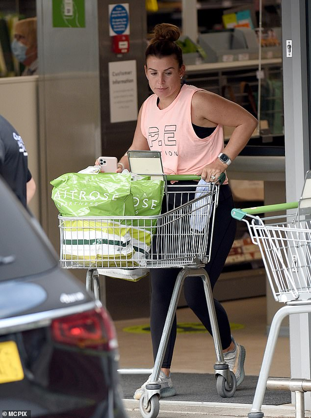 Casually-clad:She teamed her sporty look with trainers and wore a black vest underneath her pink top