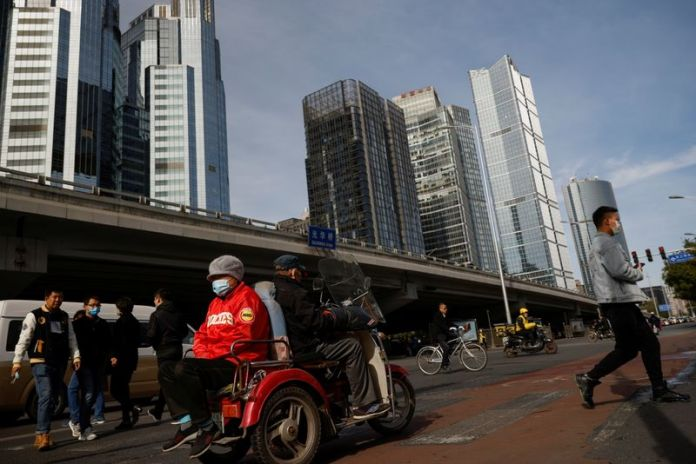 © Reuters. FILE PHOTO:  Elderly people cross a street in a tricycle in the Central Business District (CBD) following an outbreak of the coronavirus disease (COVID-19) in Beijing