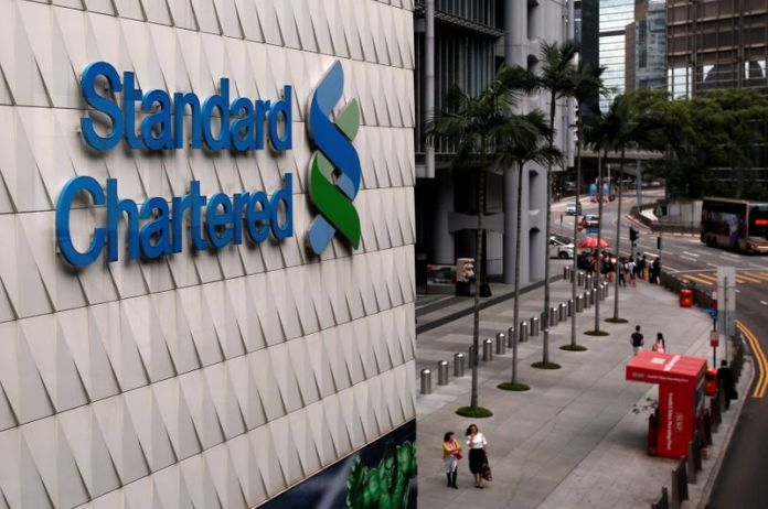 © Reuters. People walk outside the main branch of Standard Chartered in Hong Kong