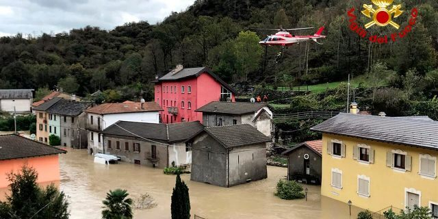 In this image made available Sunday, Oct. 4, 2020, a firefighters' helicopter flies over flooding in the town of Ornavasso, in the northern Italian region of Piedmont. (Firefighter Vigili del Fuoco via AP)