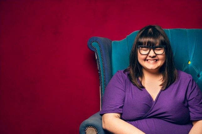 Image shows a woman with glasses and eyes closed tightly, grinning while on a blue chair