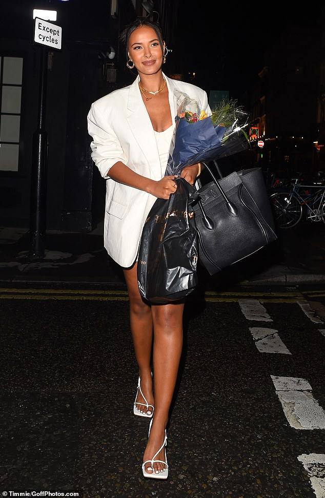 Glam goddess: Maya Jama put on a leggy display in a white mini dress and blazer as she carried a huge bunch of flowers after filming at Ronnie Scott's Jazz Club in London on Monday