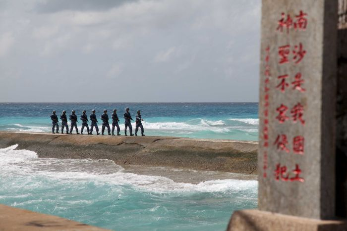 """Chinese soldiers patrol in the Spratly Islands, near a sign saying the land is """"sacred and inviolable."""""""