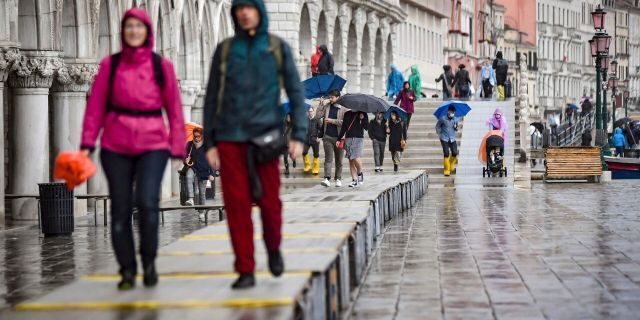 Visitors walk on on a trestle bridges during an expected high water, in Venice, northern Italy, Saturday, Oct. 3, 2020.