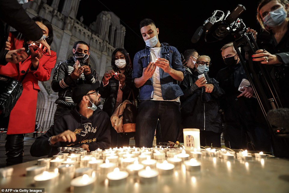 People light candles outside the Notre-Dame de l'Assomption Basilica in Nice following an Islamist terror attack