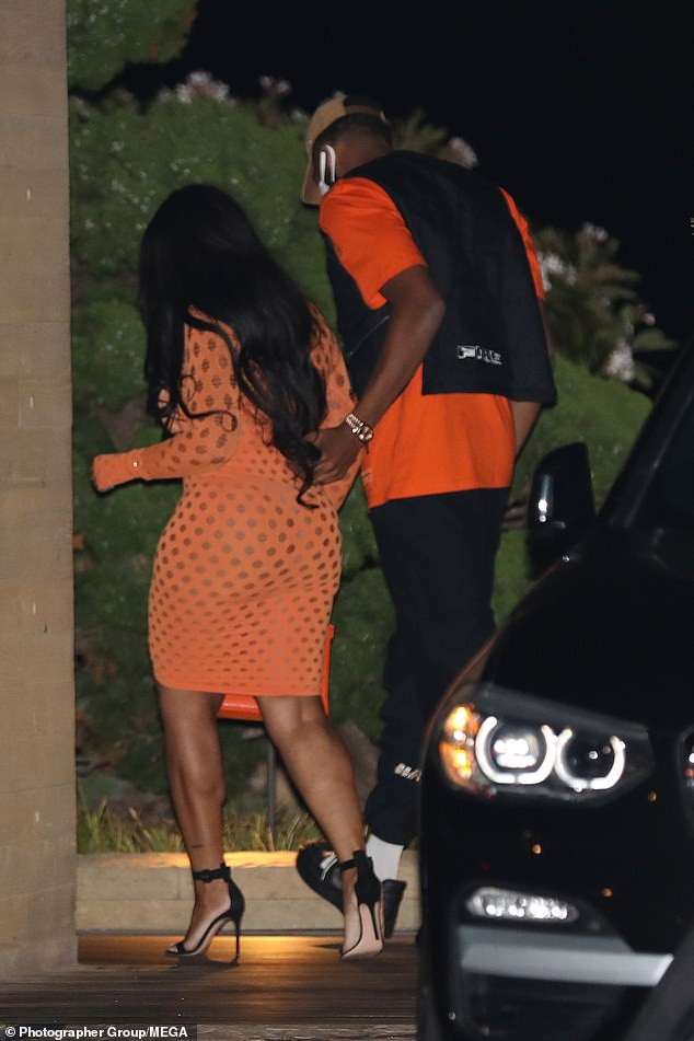 Fashion: Jordyn's gym-honed figure was on display in a see-through orange dress which featured long sleeves and a knee-length hem