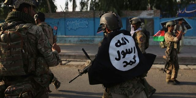 An Afghan security personnel covers himself with the Islamic State group's flag after an attack in the city of Jalalabad, east of Kabul, Afghanistan, Monday, Aug. 3, 2020. (AP Photo/Rahmat Gul)