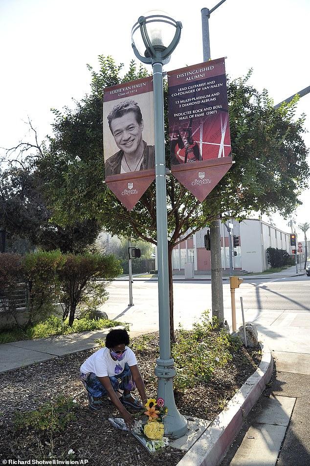Mourner Daniel Gaither laid a bouquet of flowers below a banner featuring distinguished Pasadena City College alumnus Eddie Van Halen