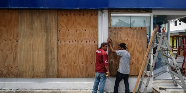 Men board up a Telcel phone store as Hurricane Delta approaches Puerto Juarez, Cancun, Mexico, Tuesday, Oct. 6, 2020.