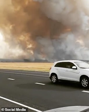 A plume of smoke passes over a road