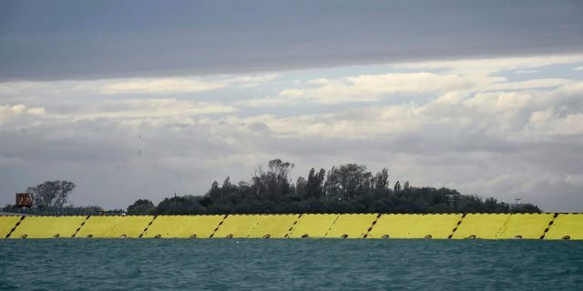 Yellow barriers are raised during high water in Venice, northern Italy, Saturday, Oct. 3, 2020.