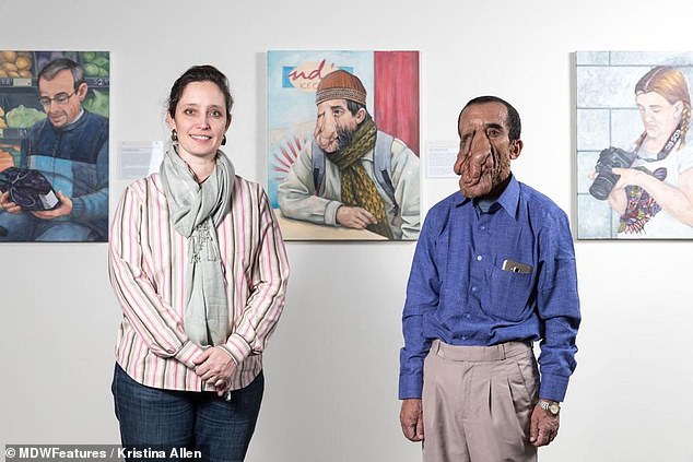Ashok stands with Rachel Mindrup, the artist behind the portrait of Ashok on display in the Nebraska art gallery, seen on the wall behind them