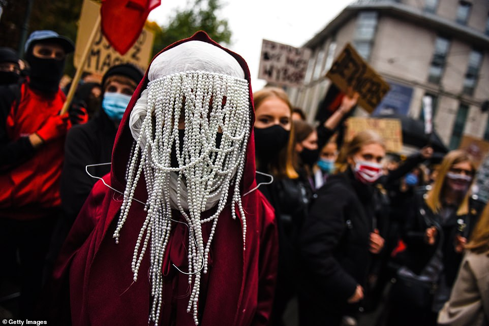 A woman wearing clothes resembling a burka and the robes of a handmaid from 'Handmaid's Tale' - with a coat hanger around her neck - protests on the fourth day of demonstrations against Poland's abortion laws in front of Krakow's Archbishop's Palace on October 25