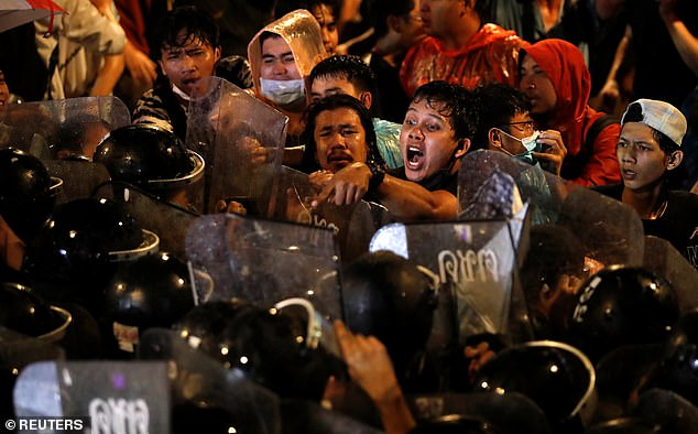 People scuffle with police in Bangkok last Friday as the king's rare visit from Germany coincided with anti-government protests and clashes between royalists and pro-democracy activists