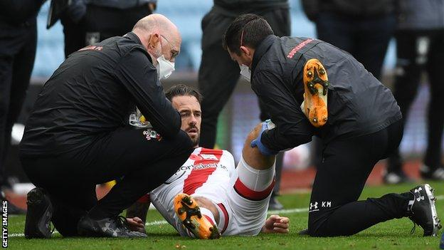 Southampton striker Danny Ings receives treatment from two physios after injuring his left knee against Aston Villa