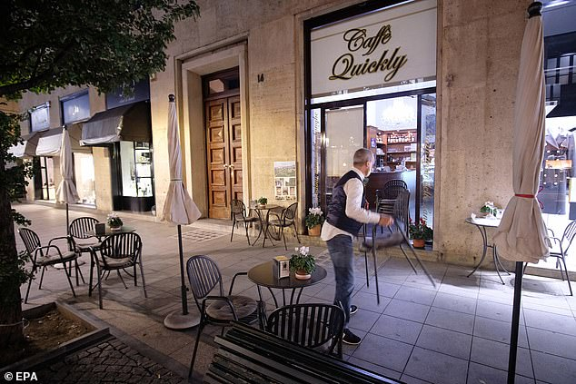 An owner prepares to close his restaurant in the center of Turin, Italy, 30 October 2020